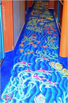 In the hallway carpet, the fish swim toward the front of the ship.