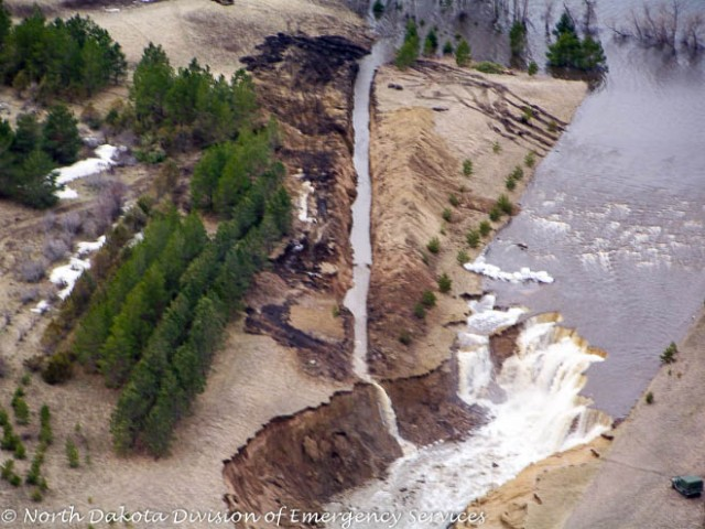 An earthen dam outside a small community was in danger of failing due to the spillway being washed away.