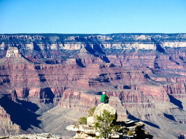 The climbers on the rock outcropping help to demonstrate the immense scale of the Grand Canyon.