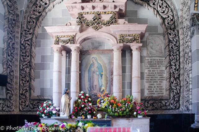 At the rear of the church a small altar is adorned with fresh flowers.