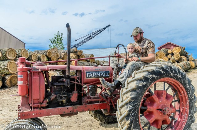 A boy and his dad spend quality time on the old Farmall.