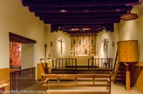 A chapel in the museum is adjacent to a room displaying a wide variety of cruicifixes.