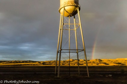 A partial rainbow near an old water tower.