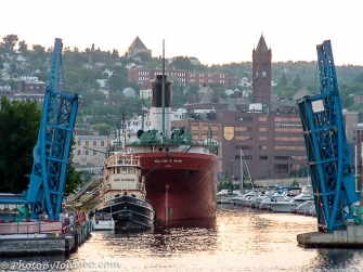 An open drawbridge frames a freighter and the skyline at Duluth, Minnesota.