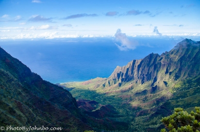 The mountainous landscape and light clouds frame this view of the Na Pali Coast on Kauai, Hawaii.