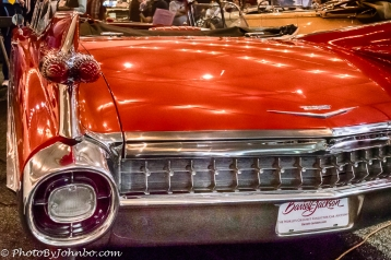 The iconic tail fin and rear deck of a 1959 Cadillac convertible.